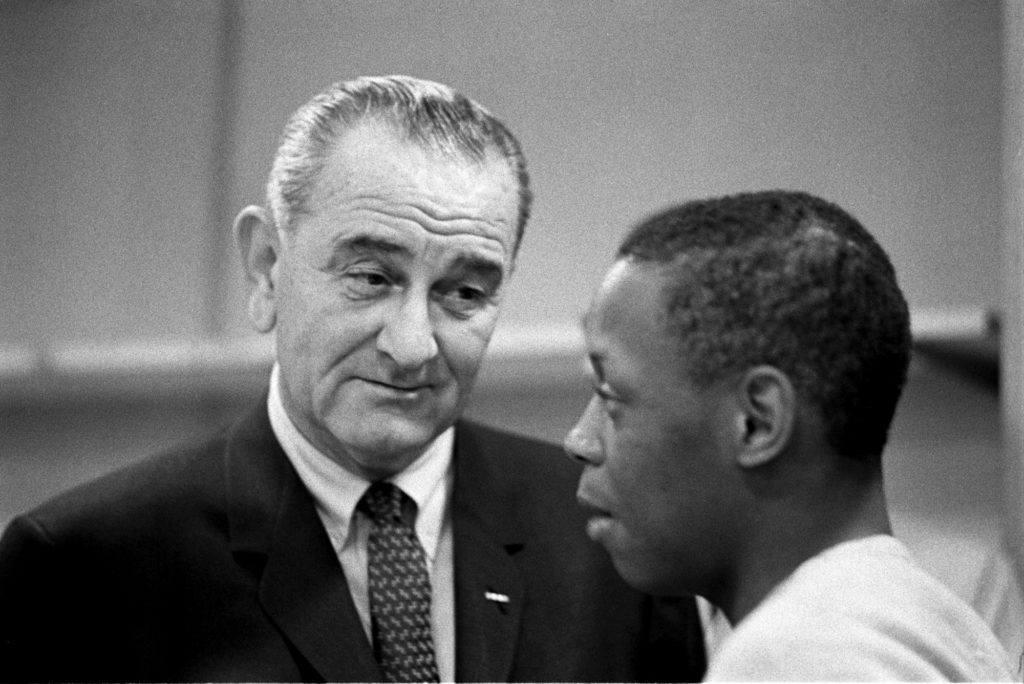 President Lyndon B. Johnson talks to corpsmen at Catoctin Job Corps Conservation Center, March 10, 1965. Photograph by Yoichi Okamoto. Source: LBJ Library.